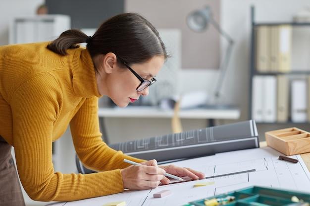 사무실에서 책상에서 작업하는 동안 청사진을 그리는 여성 건축가의 측면보기 초상화,