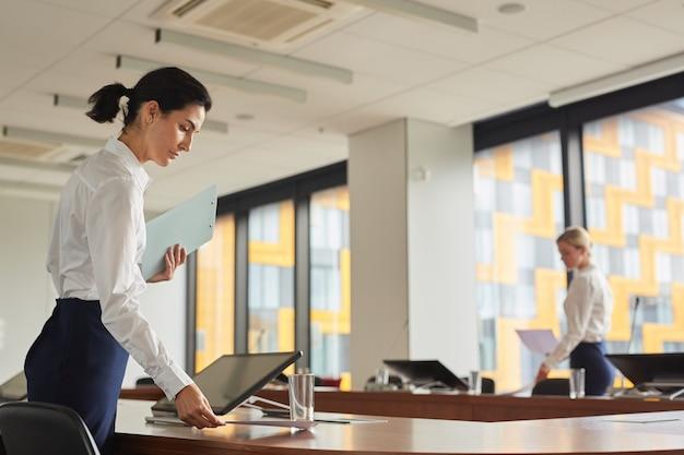 Портрет вид сбоку женщин-помощниц, раскладывающих документы на столе на столе во время подготовки конференц-зала для делового мероприятия,