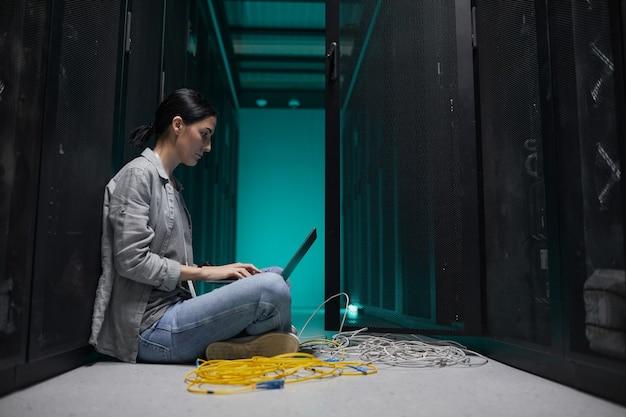 Портрет женщины-инженера по обработке данных с ноутбуком, вид сбоку, сидя на полу в серверной и настраивая суперкомпьютерную сеть, скопируйте пространство