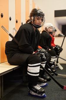 Вид сбоку портрет женской хоккейной команды, сидящей в ряду