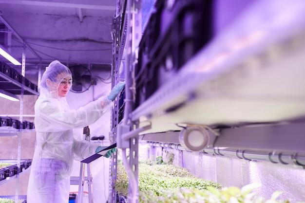 보육 온실 또는 농장 실험실에서 작업하는 동안 클립 보드를 들고 여성 과학자의 측면보기 초상화, 복사 공간