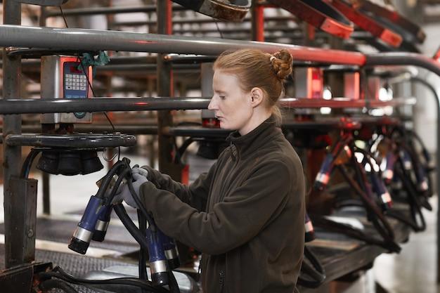 현대 낙농 농장에서 젖 짜는 기계를 설정하는 여성 노동자의 측면보기 초상화, 복사 공간