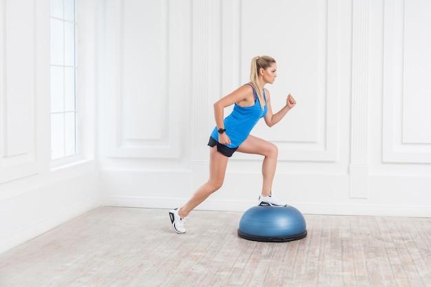 검은 반바지를 입고 체육관에서 일하는 파란색 상의에 집중된 스포티한 젊은 운동 금발 여성의 측면 보기 초상화는 bosu 균형 트레이너에서 운동을 하며 피트니스 공에서 한 발짝 나아갑니다. 실내, 스튜디오 촬영