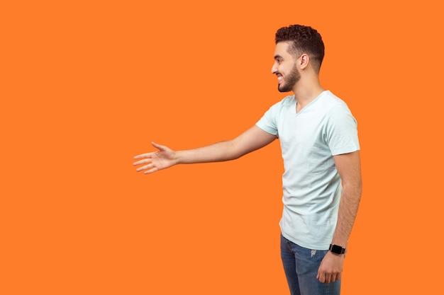 握手と挨拶に手を差し伸べる白いtシャツのひげを持つフレンドリーなポジティブな男性の側面図の肖像画、テキスト用の左側の空のコピースペース。オレンジ色の背景に分離された屋内スタジオショット