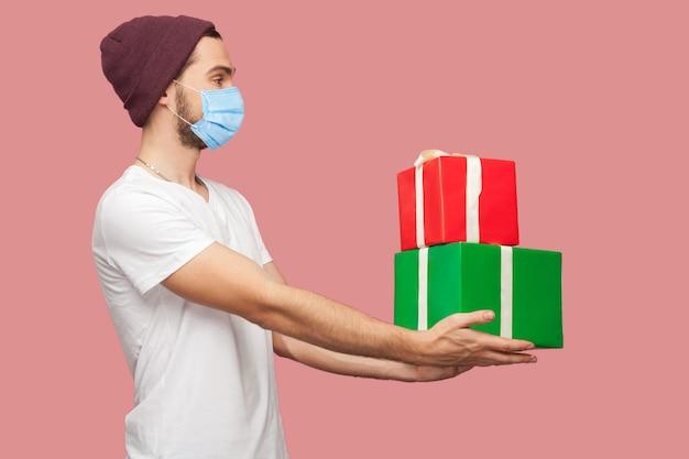 흰색 셔츠에 외과용 의료 마스크를 쓰고 캐주얼 모자를 쓰고 서 있는 친근한 젊은 힙스터 남자의 측면 초상화는 두 개의 선물 상자와 미소를 제공합니다. 실내, 절연, 스튜디오 촬영, 분홍색 배경