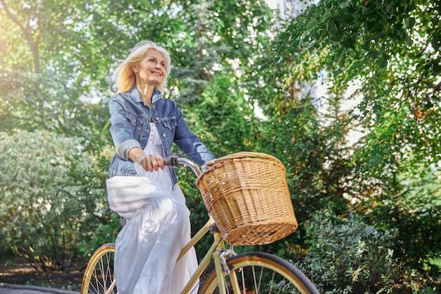 空の街の大通りで彼女のビンテージバイクのペダルを押すデニムジャケットのゴージャスな女性の側面図の肖像画