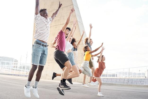 Портрет вид сбоку группы счастливых многонациональных друзей, весело проводящих время. юные студенты прыгают за пределы университета.