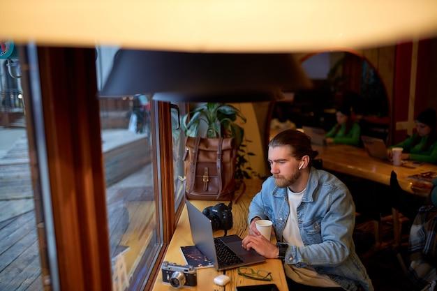 노트북에서 작업 하는 데님 재킷에 잘생긴 백인 남자의 측면 보기 초상화 초점