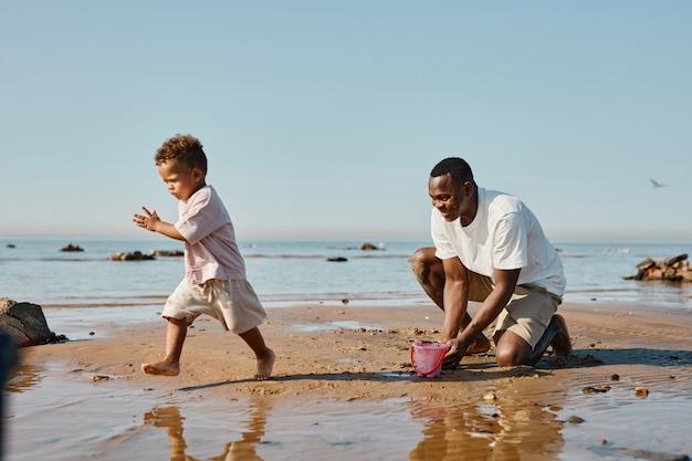 ビーチのコピースペースで走っている男の子と遊ぶ幸せなアフリカ系アメリカ人の父の側面図の肖像画