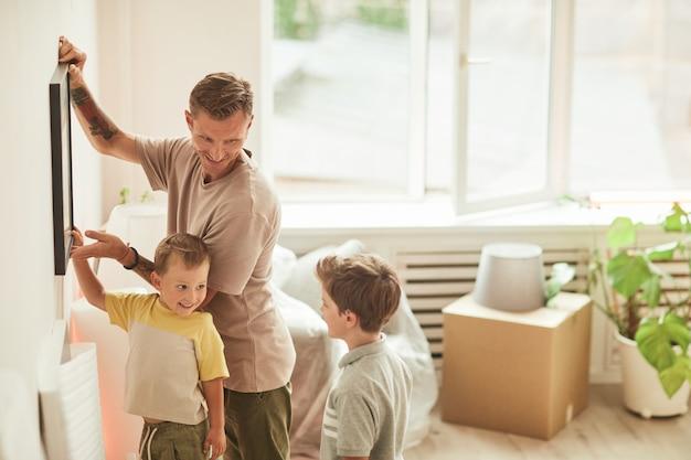 Вид сбоку портрет счастливого отца с двумя сыновьями, висящими на стене картинами во время переезда в новый дом ...