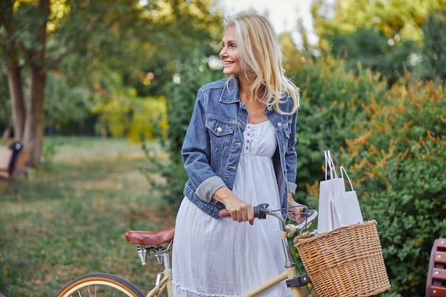 도시 광장에서 복고 자전거를 타고 웃고 있는 행복한 금발 백인 여성의 측면 초상화
