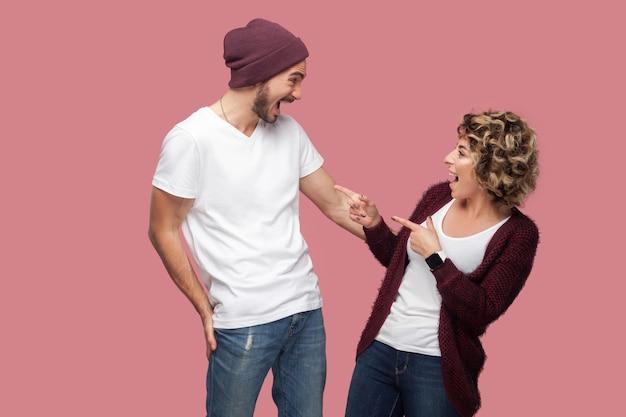 Портрет взгляда со стороны счастливой удивленной пары друзей в положении непринужденного стиля, женщина указывая пальцами на мужчину с открытым ртом и возбужденная. изолированный, закрытый, студийный снимок, розовый фон
