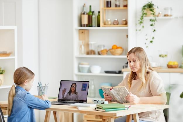 家庭教師や教師とオンラインクラスでラップトップを使用している少女の側面図の肖像画は、母親が彼女を見ている居心地の良いキッチンのインテリアの机に座って、スペースをコピーします