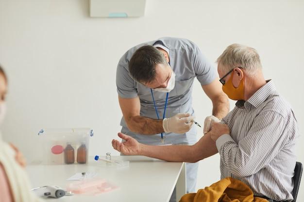 의료 클리닉에서 마스크를 쓴 노인에게 예방 접종을 하는 남성 의사의 측면 초상화, 복사 공간