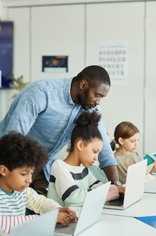 Портрет вид сбоку учителя-мужчины, помогающего детям использовать компьютеры в ит-классе