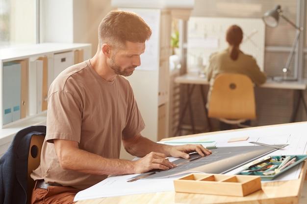 Портрет вид сбоку зрелого бородатого архитектора, смотрящего на чертежи, сидя за чертежным столом в солнечном свете,