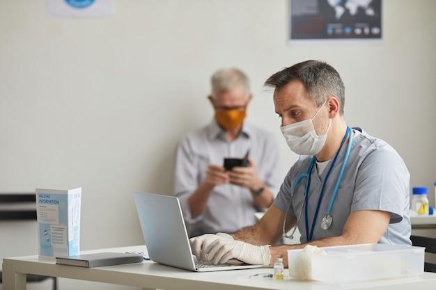 클리닉이나 백신 접종 센터에서 환자를 기다리는 동안 마스크를 쓰고 노트북을 사용하는 성숙한 남성 의사의 측면 초상화, 복사 공간