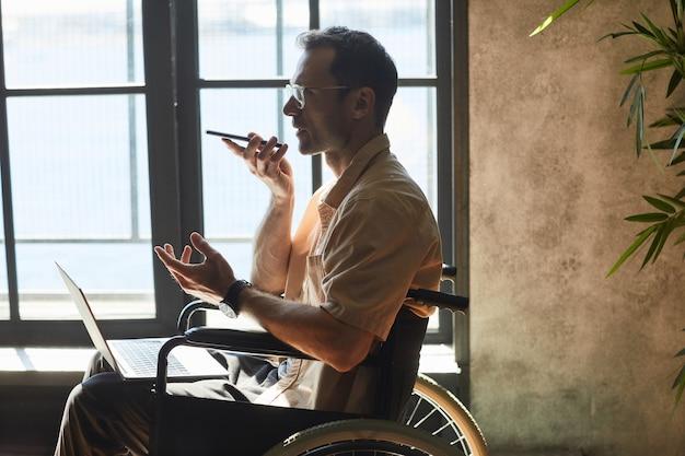 窓際、コピースペースで自宅で作業しながらスマートフォンを使用して車椅子で現代の成人男性の側面図の肖像画