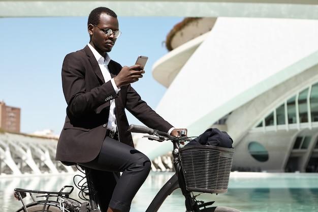 のんきでうれしそうな顔つきで、自転車に乗って通勤する、環境に配慮した現代のアフロアメリカンバンカーの側面図の肖像。自転車に乗ってフォーマルな服装で魅力的な黒人実業家