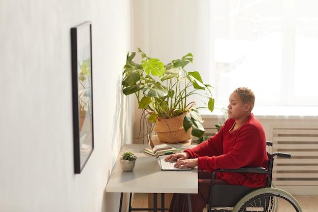 日光に照らされた机、コピースペースで自宅で仕事をしながら車椅子を使用して現代の混血の女性の側面図の肖像画