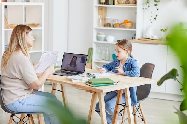 机に座ってオンラインの学校のビデオを見ながらかわいい娘と宿題をしている母親の側面図、コピースペース
