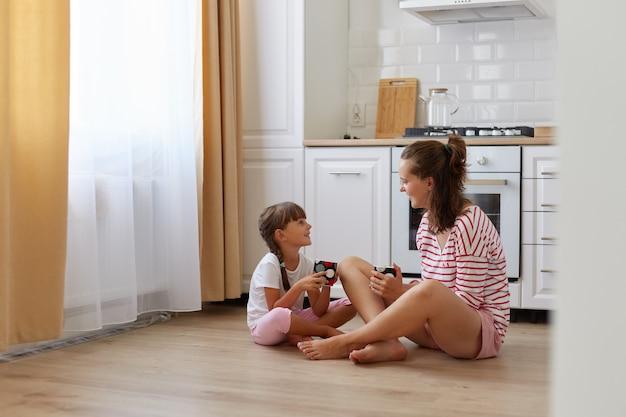 Вид сбоку портрет матери с дочерью ребенка, сидящей на полу на кухне и пьющей горячий напиток, разговаривая вместе, проводя время дома.