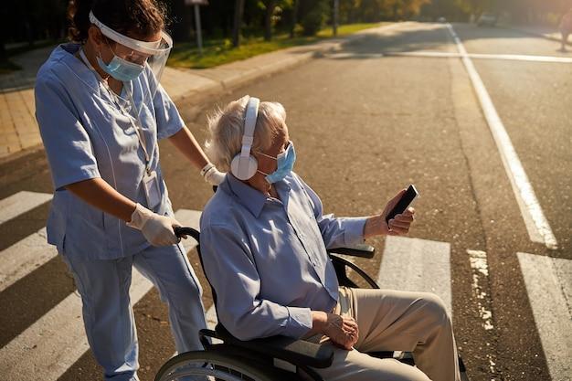 Вид сбоку портрет пожилого мужчины в наушниках, который что-то слушает, пока женщина-медицинский работник гуляет с ним по городу