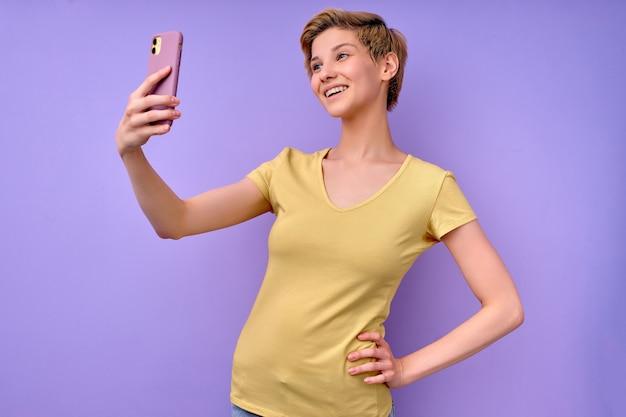 携帯電話のスマートフォンselfieで写真を撮る楽観的な白人女性の側面図の肖像画...