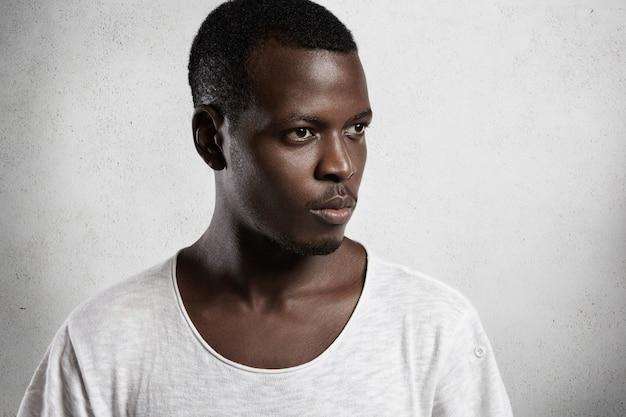 白いコンクリートの壁に対して隔離されたポーズをとって深刻な自信を持って表情で彼の前を見て低ネックラインと白いtシャツを着て物思いに沈んだアフリカ人の側面図の肖像画