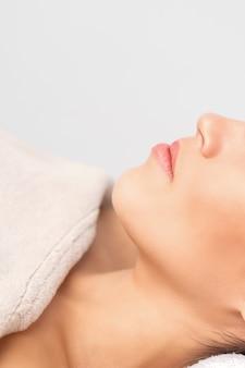 Портрет вид сбоку задумчивой молодой женщины, лежащей и ожидающей косметической процедуры в салоне красоты