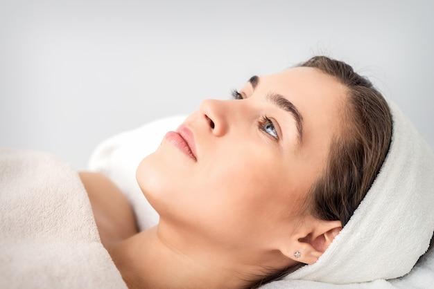 Портрет вид сбоку задумчивой молодой женщины, лежащей на столе косметолога в ожидании косметической процедуры в салоне красоты