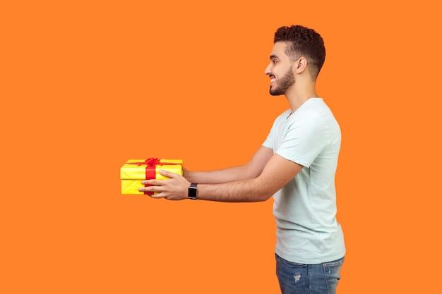 흰색 티셔츠에 수염을 기른 긍정적인 관대한 브루네트 남자의 옆모습 초상화는 웃고 선물 상자를 주고, 휴가 선물을 공유하고, 자선 개념을 제공합니다. 오렌지 배경에 고립 된 실내 스튜디오 촬영