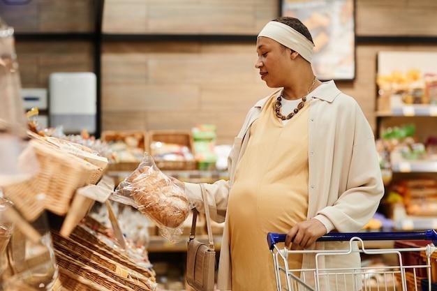 Вид сбоку портрет беременной афро-американской женщины, покупающей свежий хлеб во время покупки продуктов в супермаркете, копией пространства