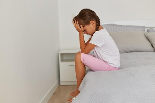 흰색 티셔츠를 입은 슬픈 여자 아이의 옆모습 초상화는 머리를 숙이고 머리를 숙이고 얼굴을 가리고 화를 내며 슬픔을 표현하는 분홍색 짧고 검은 머리 아이입니다.