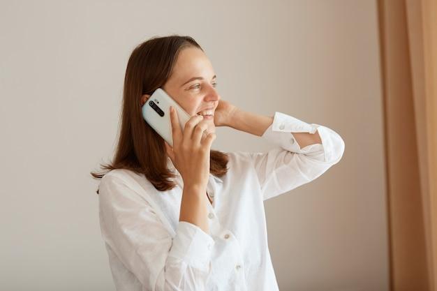 白い綿のシャツを着て、腕を上げて立って電話を話し、目をそらし、楽しい会話をしている、まっすぐな黒髪の満足している幸せな女性の側面図の肖像画。
