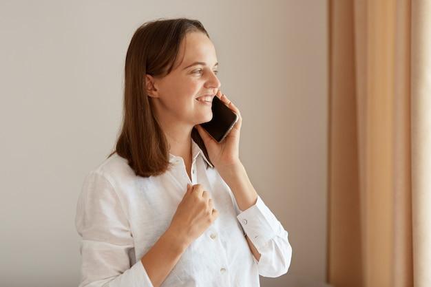 満足のいく楽観的な身に着けている白い綿のシャツを着て携帯電話を話し、前向きな表情を持ち、良いニュースを聞き、屋内でポーズをとる側面図の肖像画。