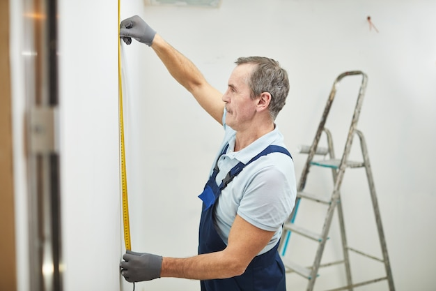Вид сбоку портрет старшего строителя, измеряющего стену во время ремонта дома, копией пространства
