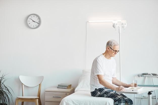 흰색 방에 침대에 앉아있는 동안 병원에서 음식을 먹는 노인의 측면보기 초상화, 복사 공간