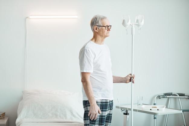 병실에서 iv 드립 스탠드를 들고 생각에 잠겨 멀리 바라보는 노인의 측면 초상화, 복사 공간