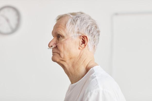산소 지원 튜브에 초점을 맞춘 병원에 있는 노인의 측면 초상화, 복사 공간