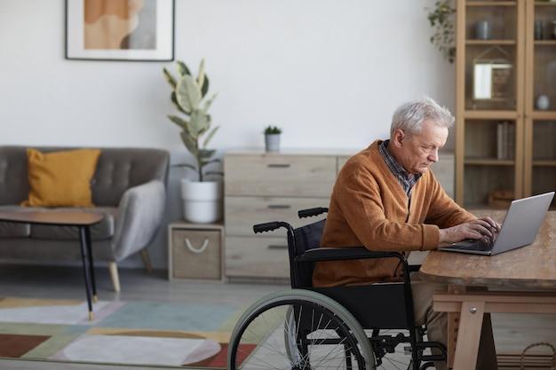 家のインテリア、コピースペースの机で作業中にラップトップを使用して車椅子の年配の男性の側面図の肖像画