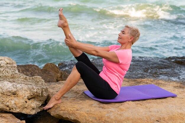 Вид сбоку портрет старшей женщины на пляже