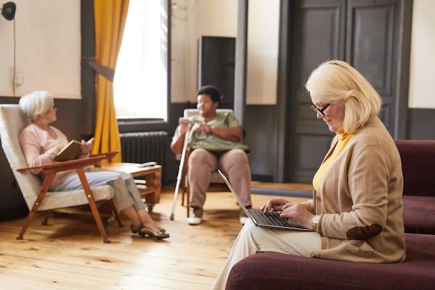 Вид сбоку портрет пожилой женщины, использующей ноутбук во время отдыха в доме престарелых с копией пространства