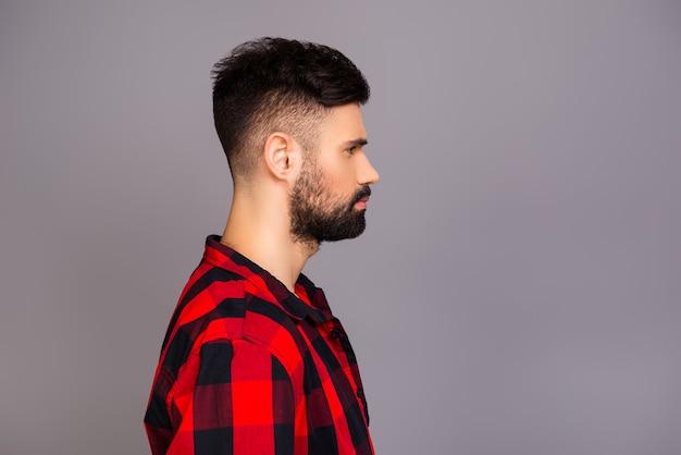 赤い市松模様のシャツを着た真面目な男の側面図の肖像画
