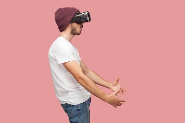 흰 셔츠, 캐주얼 모자 서, vr을 입고, 비디오 게임을 하고, 무언가를 만지려고 하는 충격을 받은 수염난 청년의 측면 초상화. 실내, 절연, 스튜디오 촬영, 분홍색 배경