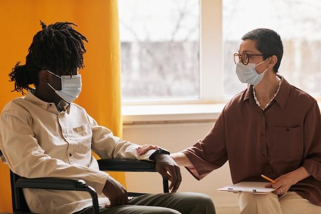 클리닉에서 치료 회의 중 남성 환자를 지원하는 짧은 머리 여성 심리학자의 측면 초상화, 둘 다 마스크를 착용