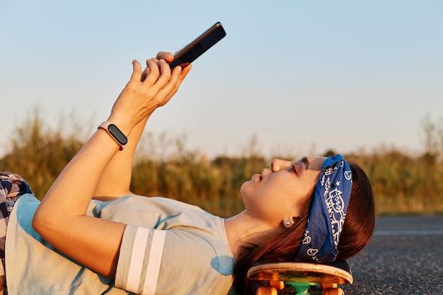 머리띠와 티셔츠를 입고 아스팔트 길에 누워 스케이트보드에 머리를 대고 손에 전화를 들고 셀카를 찍거나 인터넷을 검색하는 날씬한 아름다운 여성의 측면 초상화.