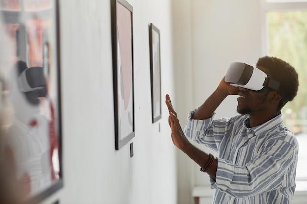 Портрет улыбающегося афроамериканца в vr-снаряжении, вид сбоку, наслаждаясь иммерсивным опытом на выставке галереи современного искусства,