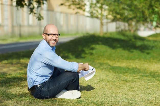 야외에서 푸른 잔디에 앉아 햇빛을 즐기면서 카메라를보고 웃는 대머리 남자의 측면보기 초상화, 복사 공간