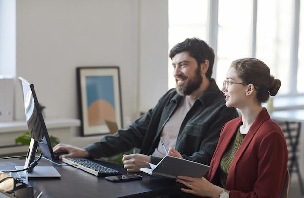 Портрет улыбающегося бородатого бизнесмена, разговаривающего с коллегой-женщиной во время встречи за столом в офисе, вид сбоку